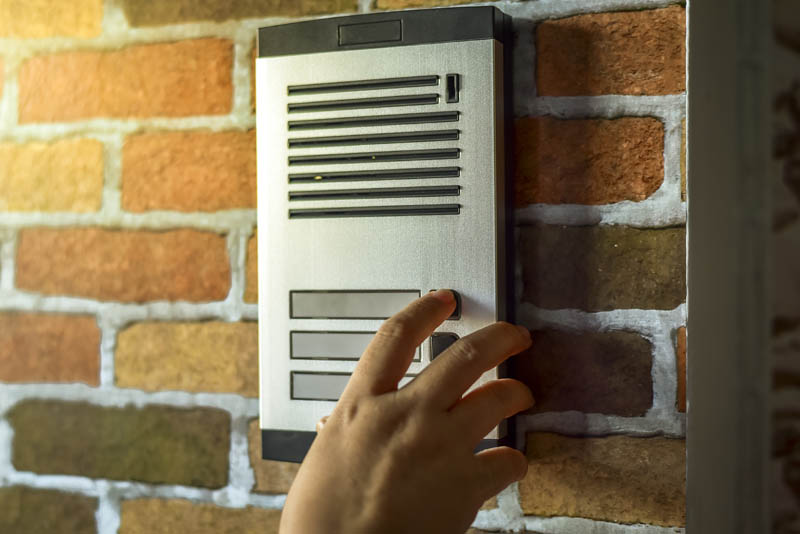 hand touching button on intercom system