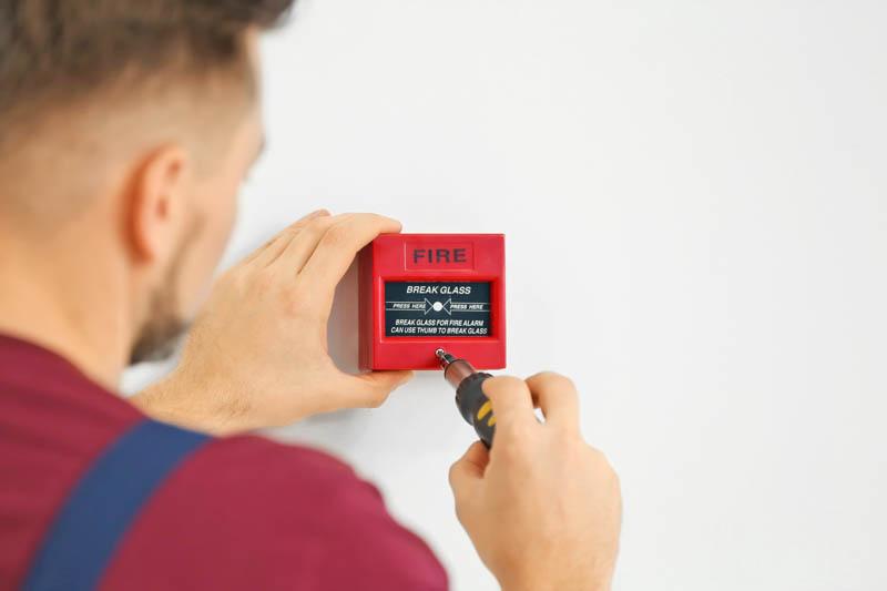 man installing break glass fire alarm on white wall