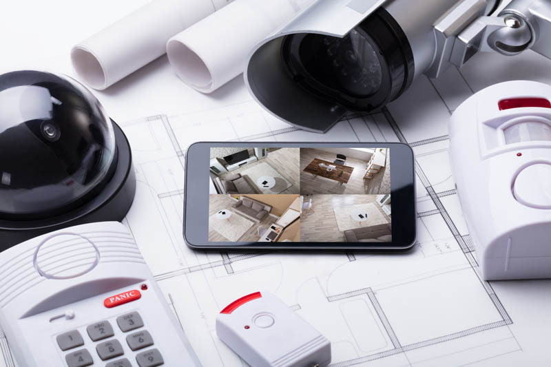 mobile phone showing cctv surveillance on table with security equipment