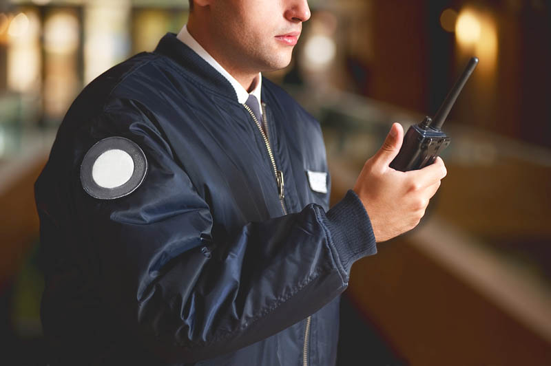 security guard in building using handheld transceiver